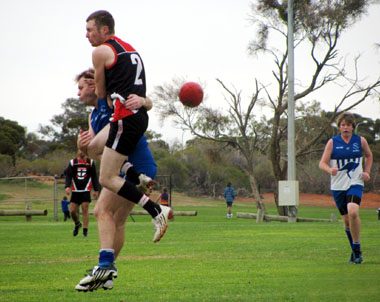 A tackle involving Jack Burns and Andamooka player, with Kendall Plant in the background