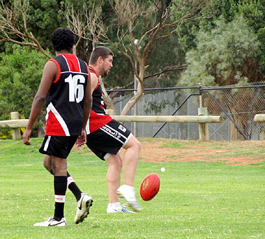 Ben Buller kicking for goal with Timmy Walker  watching