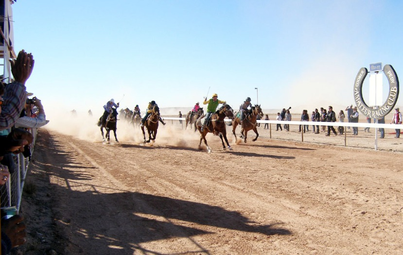Kingston Sea emerges from the dust filled track carrying jockey Garry Burchmore past the post to his third Coober Pedy Opal Inn Cup win
