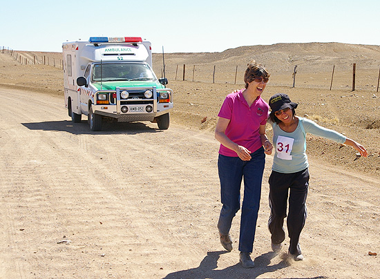 Judy Underwood and Elsie Carboni share a joke as they walk their distance past the Dingo Fence with Ambulance close behind
