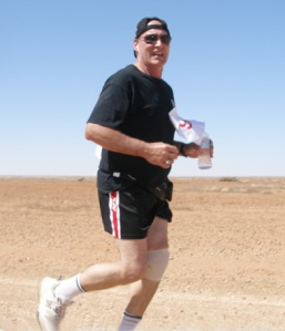 Steve Baines, Coober Pedy's Mayor jaunts along with Coober Pedy now visible and team mates well behind