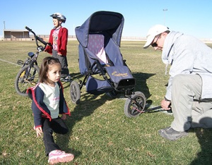 Steve Staines pumps up the stroller tyres in case Skye needs a lift. Giordan ready to go on his bike