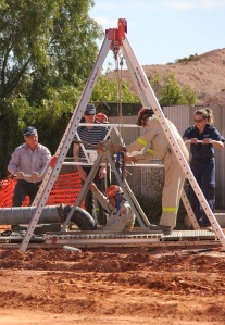 Police and Coober Pedy Mine Rescue volunteers uncover two more shafts at location on Monday - seen here entering one of the shafts