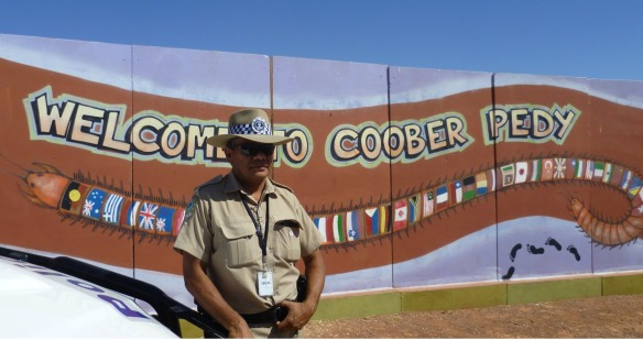 A police officer stands at the welcome sign in Coober Pedy